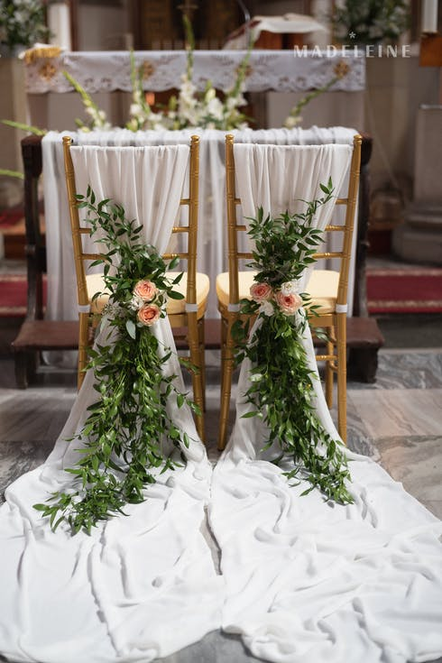 Chairs of the bride and groom decorated with tulle